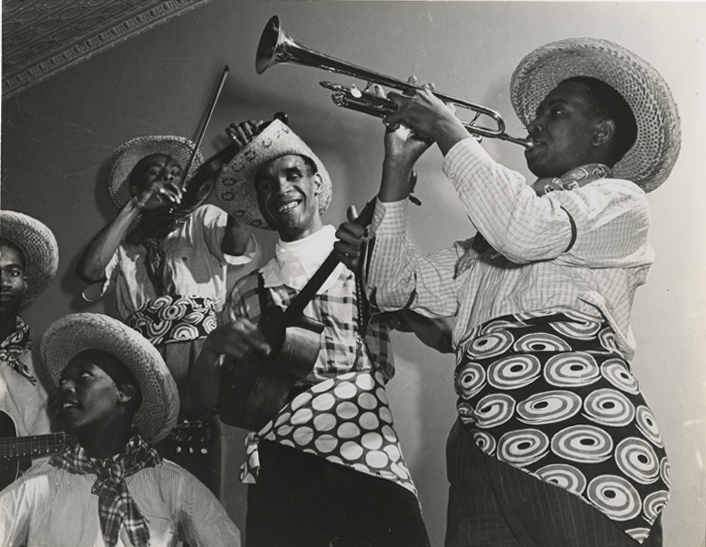 "The Duke of Iron (center) and his Trinidad Calypso Troubadors, preparing for an engagement at the Pago Pago Club, New York, January 1941. The ""Calypso Kid"" (Bill Matons; see above) and his dancers joined the Duke for this engagement.  Credit: New York Journal-American Photo Morgue, Harry Ransom Center, University of Texas at Austin. Special thanks to Linda Briscoe Myers."